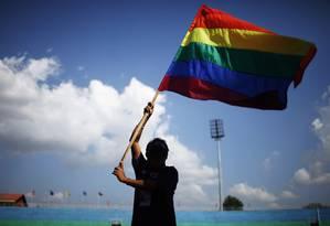 Um membro da comunidade LGBT exibe a bandeira do orgulho gay Foto: Niranjan Shrestha / AP/12-10-2012