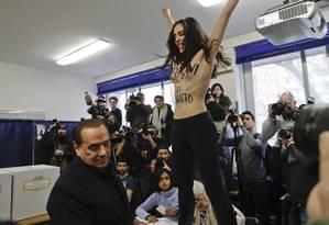 Mulher protesta contra Berlusconi dentro da seção eleitoral do ex-premier Foto: Luca Bruno / AP