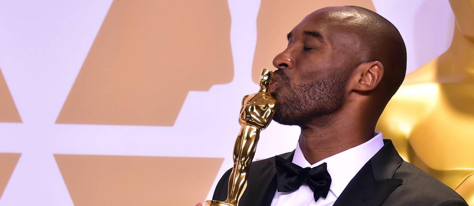Kobe Bryant beija sua estatueta do Oscar, conquistada graças ao curta 'Dear basketball' Foto: FREDERIC J. BROWN / AFP