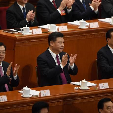 O presidente Xi Jinping (centro) e o premier Li Keqiang (direita) aplaudem durante a sessão de abertura do Congresso Nacional do Povo em Pequim: poder sem limite Foto: GREG BAKER/AFP