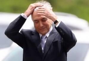 O presidente Michel Temer ajeita o cabelo antes de reunião do Conselho Militar de Defesa Foto: Montagem sobre fotos de Jorge William/Arquivo