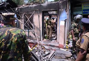 Equipe da Força-Tarefa Especial do Sri Lanka e policiais ficam de guarda perto de uma casa queimada após um conflito entre duas comunidades em Digana, distrito central de Kandy, Sri Lanka, 6 de março de 2018. Foto: STRINGER / REUTERS