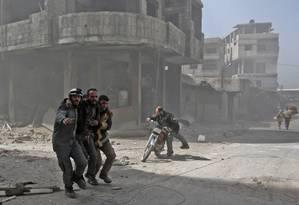 Voluntários da Defesa Civil ajudam civis durante ataques do regime em reduto rebelde de Ghouta Oriental Foto: ABDULMONAM EASSA / AFP