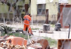 Funcionários da Comlurb colocam a barricada no lugar após a passagem do caminhão de lixo Foto: Marcio Alves / Agência O Globo