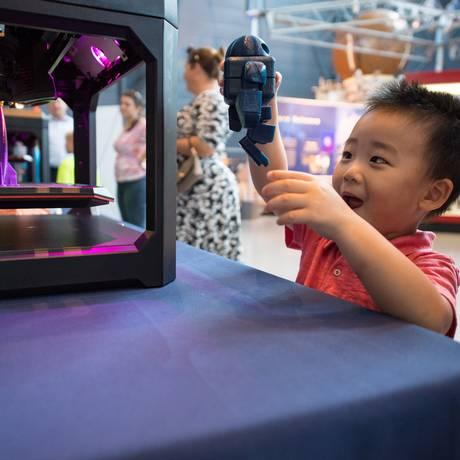 Visitante brinca com impressora 3D em edição do evento nos EUA Foto: NASA/Aubrey Gemignani / Divulgação/NASA/Aubrey Gemignani