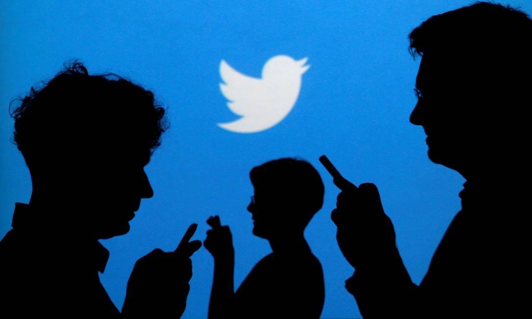 Usuários do Twitter com seus telefones: compartilhamento é ato social Foto: REUTERS/KACPER PEMPEL
