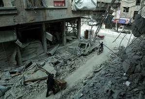 Sírios em meio a edifícios destruídos na cidade de Duma, na zona rebelde de Ghouta Oriental, perto de Damasco, em 8 de março de 2018 Foto: AFP / HAMZA AL-AJWEH