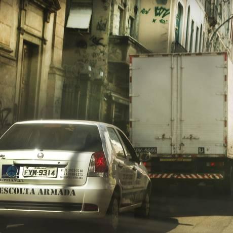 Proteção. Caminhão faz entrega no Centro do Rio com escolta armada: seguros já exigem medidas para mitigar riscos Foto: Antonio Scorza / Antonio Scorza