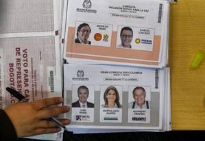 Eleitor escolhe nomes em cédulas de votação na Colômbia, onde 36 milhões de pessoas estão habilitadas para eleger parlamentares e escolher candidatos da esquerda e direita ao pelito presidencial marcado para maio Foto: AFP/LUIS ACOSTA