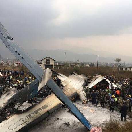 Socorristas trabalham no local onde um avião de passageiros de Bangladesh caiu em Catmandu, no Nepal Foto: Niranjan Shreshta / AP Photo