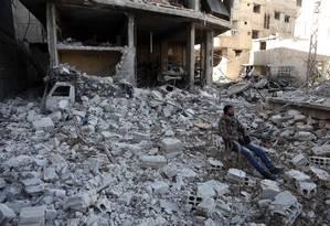 Síria se senta em meio a destroços de prédio após bombardeio das forças de Assad, em Ghouta Oriental Foto: ABDULMONAM EASSA / AFP