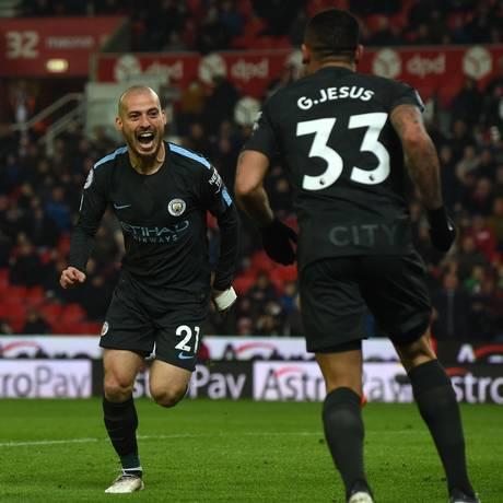 David Silva corre para abraçar Gabriel Jesus após marcar seu segundo gol na vitória do Manchester City sobre o Stoke City Foto: PAUL ELLIS / AFP