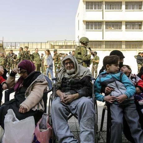 Idosos e crianças retirados de Ghouta Oriental fazem fila em posto de checagem do governo sírio perto de Damasco Foto: LOUAI BESHARA / AFP