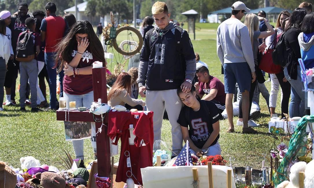 Alunos ainda sofrem com a perda de colegas de escola na Flórida em frente ao seu memorial; tragédia completa um mês neste 14 de março, e aniversário reuniu estudantes em protestos em várias partes dos EUA Foto: JOE RAEDLE / AFP