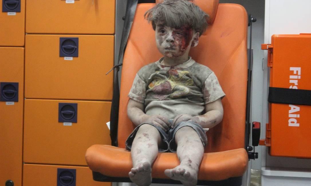 Outro menino, o pequeno Omran, chama a atenção para os horrores da guerra ao ser clicado após ser resgatado em estado de choque de um bombardeio em Aleppo, em 2016 Foto: MAHMOUD RSLAN / AFP