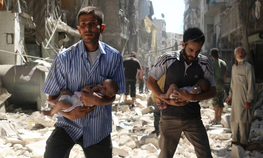 Em setembro de 2016, sírios carregam bebês em meio a bombardeios contra Aleppo: ofensiva sangrenta do regime reconquistou maior bastião rebelde da guerra, ao custo de dezenas de milhares de civis mortos Foto: AMEER ALHALBI / AFP