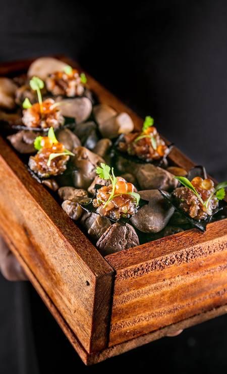 ino. Os nachos neros ganham ovas que espocam na boca e são dispostos sobre umas pedras de rio, numa caixa de madeira (R$ 39) Foto: Divulkgação/Tomas Rangel / Divulgação