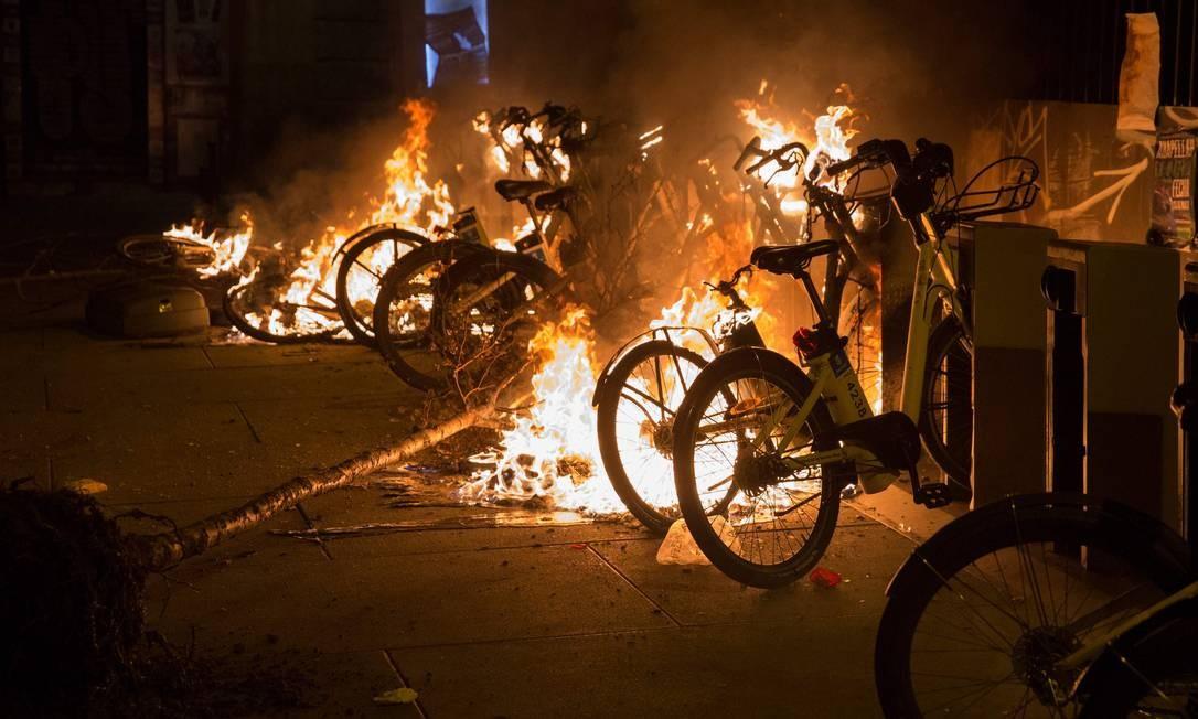 Manifestantes incendiaram bicicletas durante protesto após a morte de um vendedor ambulante senegalês no bairro Lavapiés, em Madri, na Espanha. Foto: OLMO CALVO / AFP