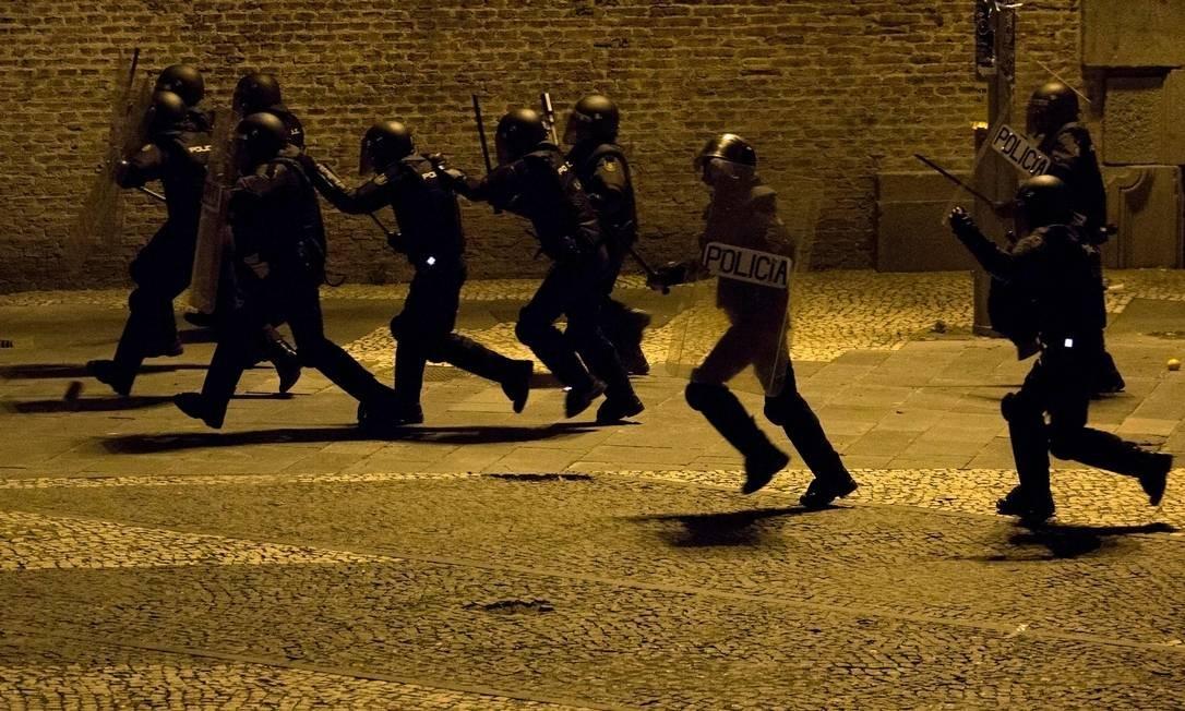 Policiais espanhóis foram enviados ao bairro de Lavapiés, em Madri, para conter manifestantes que incendiaram latas de lixo e danificaram agências bancárias Foto: OLMO CALVO / AFP