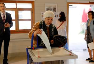 Mulher russa põe sua cédula na urna em uma seção eleitoral de Jerusalem Foto: MENAHEM KAHANA / AFP