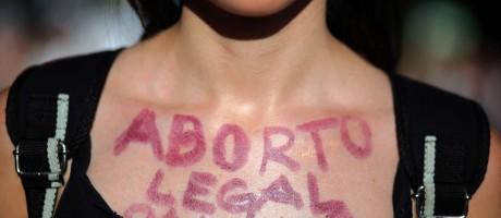 """Mulher argentina foi às ruas de Buenos Aires em 8 de março se manifestar a favor da legalização da interrupção voluntária da gravidez, com """"Aborto legal"""" desenhado no colo Foto: MARCOS BRINDICCI / REUTERS"""