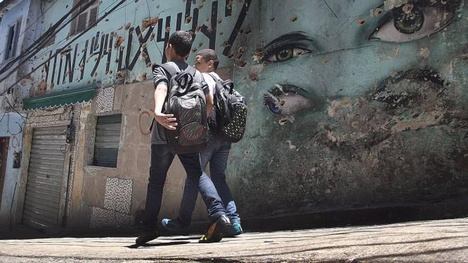 Estudantes e moradores passam diante de casa crivada de balas na Rua 2 na Rocinha durante a tentativa de invasão por grupo de traficantes, em dezembro de 2017 Foto: Antonio Scorza / Agência O Globo