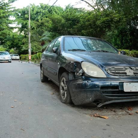 Um dos carros parados na via: pneu vazio, placa apagada e para-choque danificado Foto: Brenno Carvalho / Agência O Globo