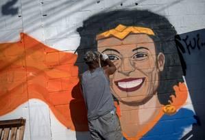 Homem grafita mural com o rosto da vereadora Marielle durante protesto na Maré Foto: Mauro Pimentel / AFP