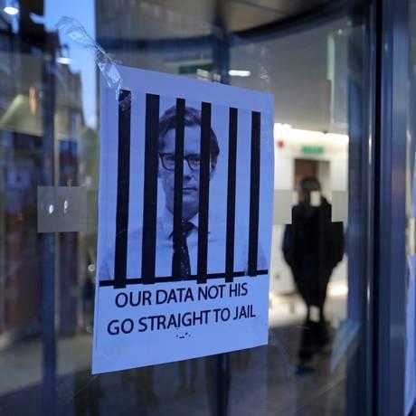 Cartazes com o rosto do CEO da Cambridge Analytica, Alexander Nix, atrás de grades, na entrada da sede da companhia, no centro de Londres Foto: DANIEL LEAL-OLIVAS / AFP