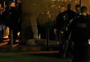 Policiais próximo ao corpo de idoso atingido por bala perdida na Rocinha Foto: Fabio Gonçalves / Agência O Globo