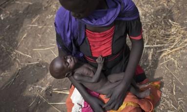 No Sudão do Sul, Adel Bol, de 20 anos, segura no colo sua filha de 10 meses de idade, Akir Mayen, em um centro de distribuição de comida em Malualkuel, nordeste do país. O Sudão é uma das nações mais ameaçadas por 'fome aguda', por conta de conflitos Foto: AP/05-04-2017