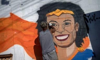 Homem grafita mural com o rosto da vereadora Marielle durante protesto na Maré: crime completa uma semana Foto: MAURO PIMENTEL / AFP