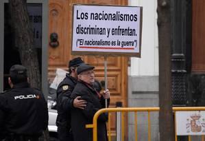 Um homem segura um cartaz com as frases