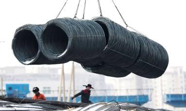 Trabalhadores em fábrica de aço Shenyang, na China. AFP