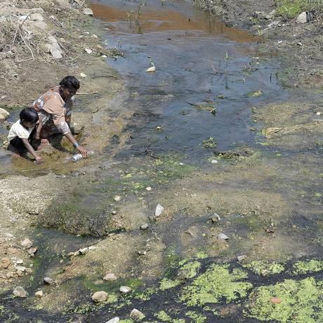 Imagem feita na Índia registra uma mulher e uma criança enchendo uma garrafa de plástico em um canal de água poluída Foto: NOAH SEELAM / AFP
