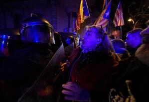 Manifestante catalã discute com policial espanhol durante protesto em Barcelona Foto: LLUIS GENE / AFP