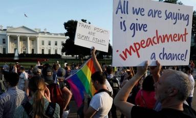 """Manifestantes protestaram em frente à Casa Branca, em julho de 2017, contra primeiras ideias de Trump sobre o possível banimento de pessoas trans do serviço militar. Na placa ao centro, lê-se """"Direitos dos trans são direitos humanos"""". E, à direita, lê-se """"Tudo o que estamos dizendo é para dar uma chance ao impeachment"""", pedindo a retirada do presidente do cargo Foto: JONATHAN ERNST / Reuters/26-07-2017"""