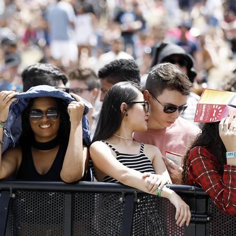 Público se protege do sol forte no Lollapalooza Foto: Lucas Tavares / Agência O Globo