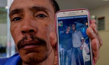 Na foto, o pai Márcio Duarte mostra a foto do filho Matheus da Silva Duarte Foto: Marcelo Regua / Agência O Globo