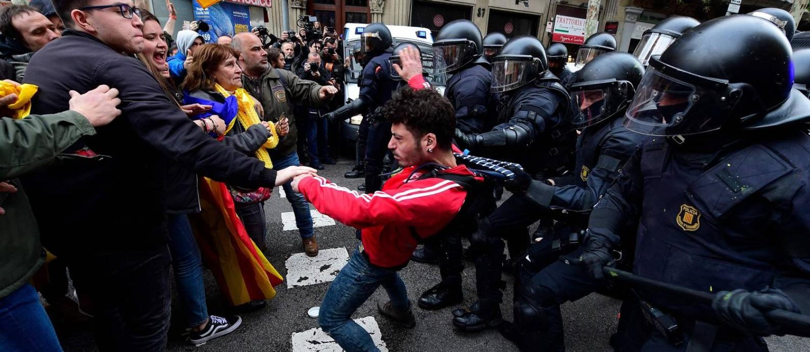 Manifestante é puxado por policiais em Barcelona Foto: LLUIS GENE / AFP
