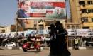 Sem opositores. Mulheres egípcias passam por pôsteres de campanha do presidente Abdel-Fattah al-Sisi, no Cairo Foto: AMMAR AWAD / REUTERS