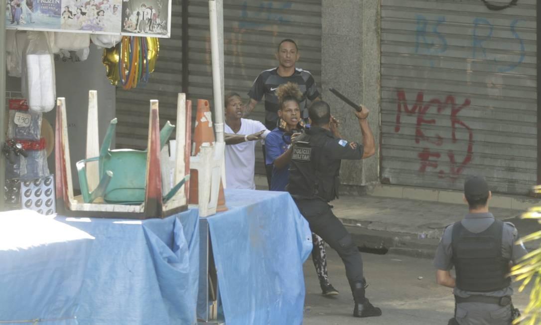 Policial em confronto com os moradores. Ana Letícia acusa policiais de apreenderem seu celular durante a confusão Foto: Gabriel de Paiva / Agência O Globo