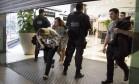 Na foto, clientes ainda dentro do estabelecimento com policiais a procura dos bandidos em 26/03 Foto: Uanderson Fernandes / Agência O Globo