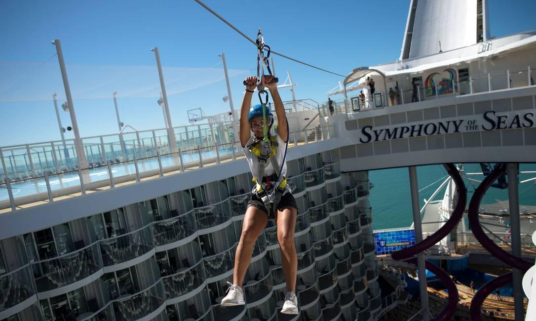 """Mulher desce por uma tirolesa a bordo do navio de cruzeiros """"Symphony of the Seas"""", da Royal Caribbean, apresentado para a imprensa nesta terça (27) em Málaga, no sul da Espanha. A embarcação é a maior do mundo, com 362 metros e 2.700 cabines, possui uma pista de gelo, parque aquático (com área para """"surfar"""") e quadra de basquete Foto: JORGE GUERRERO / AFP"""