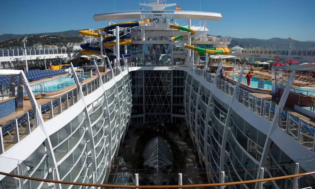 """Visão geral com as piscinas e o tobogã do """"Symphony of the Seas"""", da Royal Caribbean, apresentado para a imprensa nesta terça (27) em Málaga, no sul da Espanha. A embarcação é a maior do mundo e 2.700 cabines, possui uma pista de gelo, parque aquático (com área para """"surfar"""") e quadra de basquete Foto: JORGE GUERRERO / AFP"""