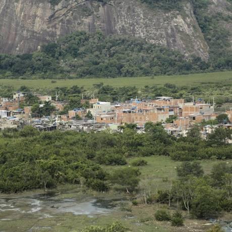 Chico City. A expansão da comunidade, que vai em direção ao rio, é acompanhada da janela por vizinhos Foto: Brenno Carvalho / Brenno Carvalho