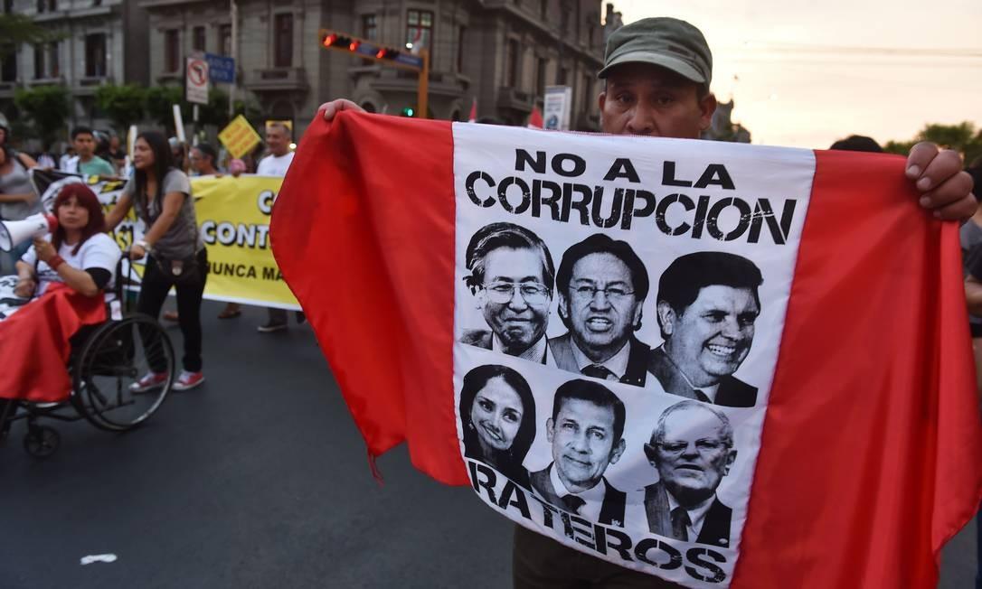 Manifestante carrega bandeira contra ex-presidentes peruanos Foto: CRIS BOURONCLE / AFP