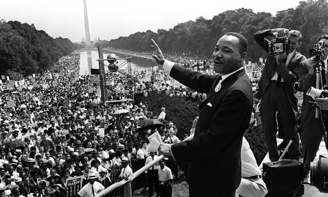 """Em 1963, Martin Luther King, líder do movimento pelos direitos civis nos EUA, acena para multidão durante a Marcha sobre Washington. O ativista liderara o boicote aos ônibus após o caso Rosa Parks e, a partir de então, foi ganhando protagonismo na luta dos negros. Neste dia, ele fez o seu mais famoso discurso, intitulado """"Eu tenho um sonho"""" Foto: AFP"""
