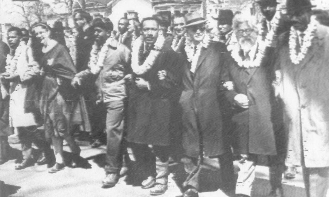 Em março de 1965, Martin Luther King caminha na marcha histórica de Selma a Montgomery. O protesto pacífico pedia o direito de voto para cidadãos negros. Na terceira tentativa de completar o trajeto, após terem sido alvo de truculência policial, os manifestantes finalmente chegaram ao Capitólio do estado do Alabama Foto: AP