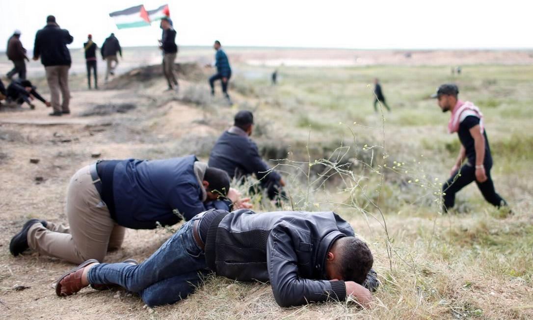 Palestinos se protegem do gás lacrimogêneo lançado pelas Forças de Defesa de Israel; agentes reforçam segurança na fronteira com Gaza durante protesto que reúne milhares de pessoas Foto: MOHAMMED SALEM / REUTERS